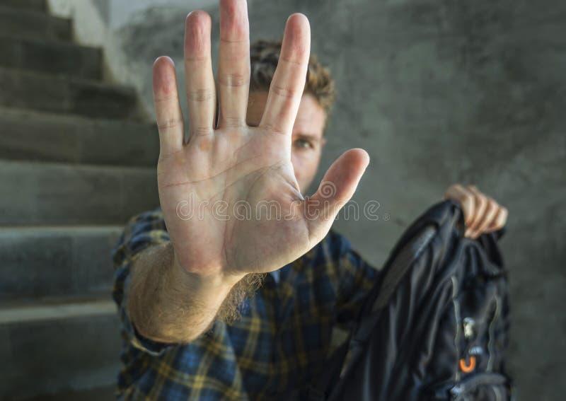 Bekämpfung von Missbrauch und Diskriminierung. junger Student mit Rucksack, der hilflos leidlos sein Gesicht bedeckt lizenzfreie stockbilder
