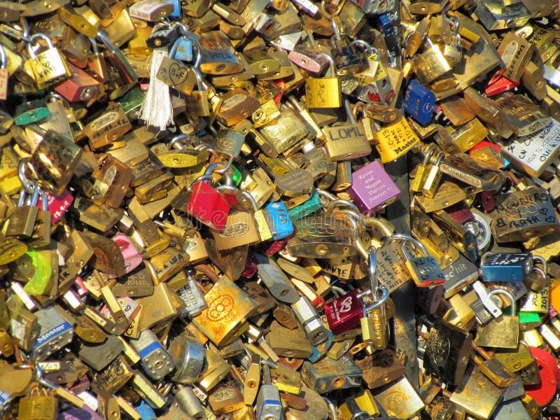 Bekanta tusentals hänglås, som förälskelselås smyckar den Pont des Arts bron i Paris, Frankrike Solig bakgrund för guld- hänglås  royaltyfri foto