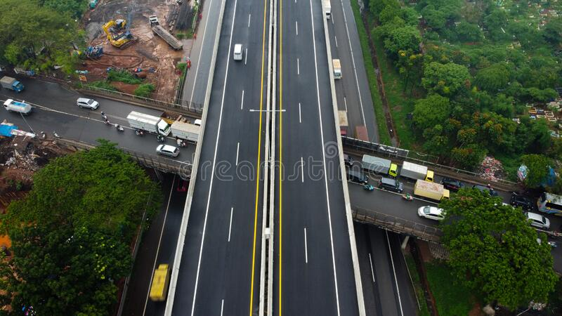 Aerial drone view of highway multilevel junction road with moving cars after rainy. Cars are blurred royalty free stock photography