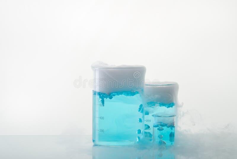 Bekers met blauw vloeibaar en droog ijs op de lijst Sublimatie van droog ijs stock fotografie
