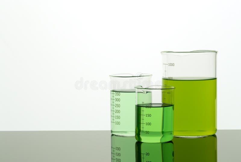 Bekers van verschillende grootte met groene vloeistof De ruimte van het exemplaar stock fotografie