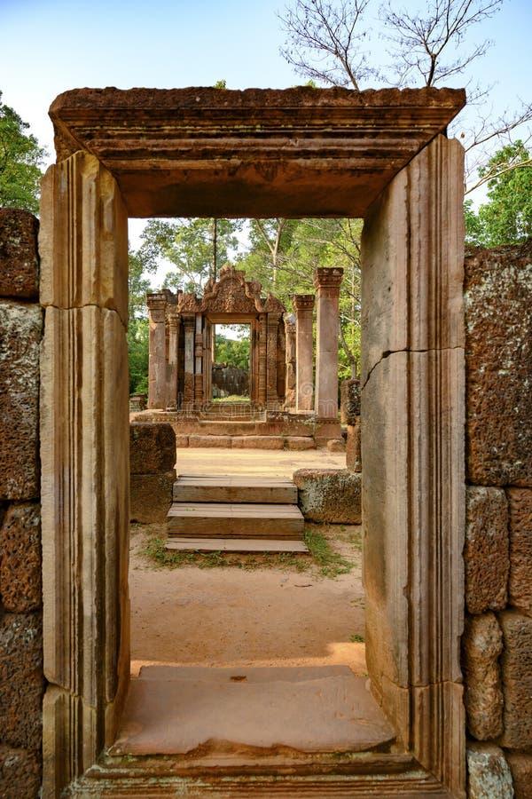 Bekijk door de tempelingang in ruïnes van Banteay Srei, Cambodja, naar het groene bos stock afbeelding