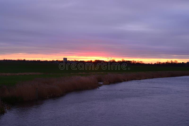 Bekijk het agrarische landschap op het nederlandse platteland in Groningen Nederland onder prachtige zonsondergang royalty-vrije stock afbeelding