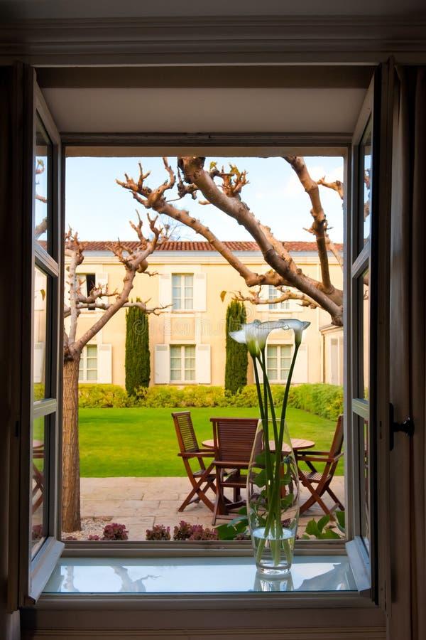 Bekijk uit het geopende raam met vaas op de achtertuin met terrasse aarde, formele tuin van Chateau Cordeillan-Bages, Bordeaux, F stock foto