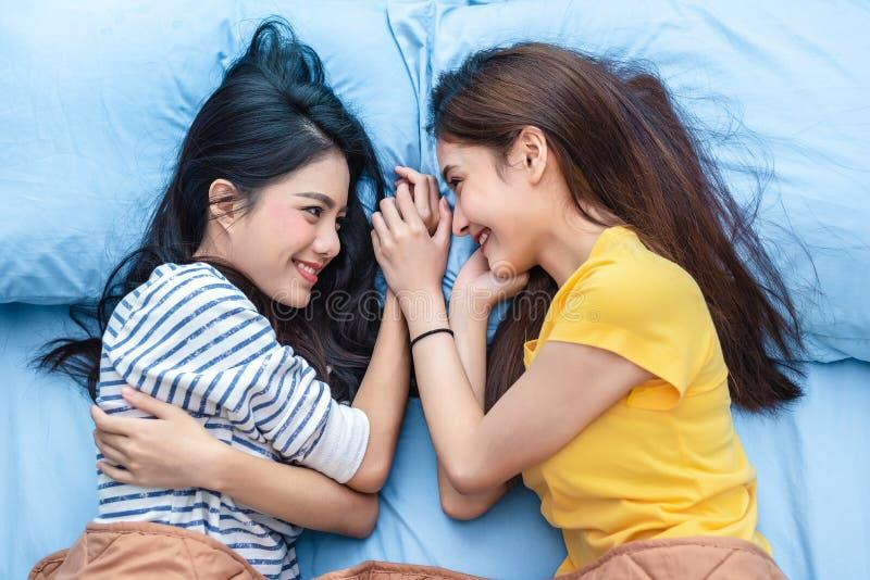 Bekijken van twee Aziatische vrouwen elke anderen wanneer het liggen op bed Levensstijlen en minnaarsconcept Het gelukleven en on stock foto