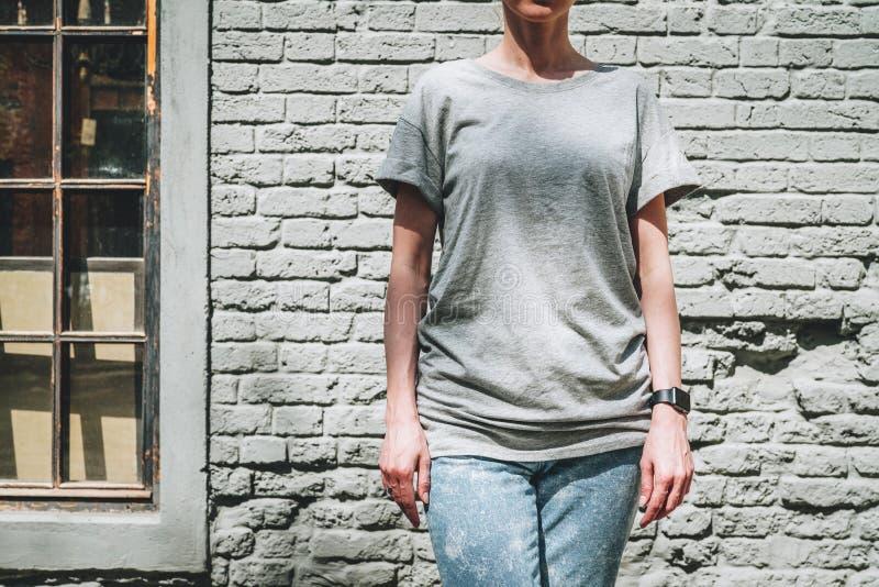 Bekläda beskådar Är den iklädda gråa t-skjortan för den unga millennial kvinnan ställningar mot den gråa tegelstenväggen royaltyfri foto