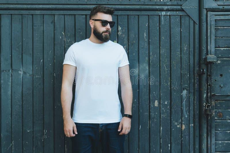 Bekläda beskådar Barnet uppsökte t-skjortan för iklädd vit för hipstermannen, och solglasögon är ställningar mot den mörka wood v royaltyfria bilder