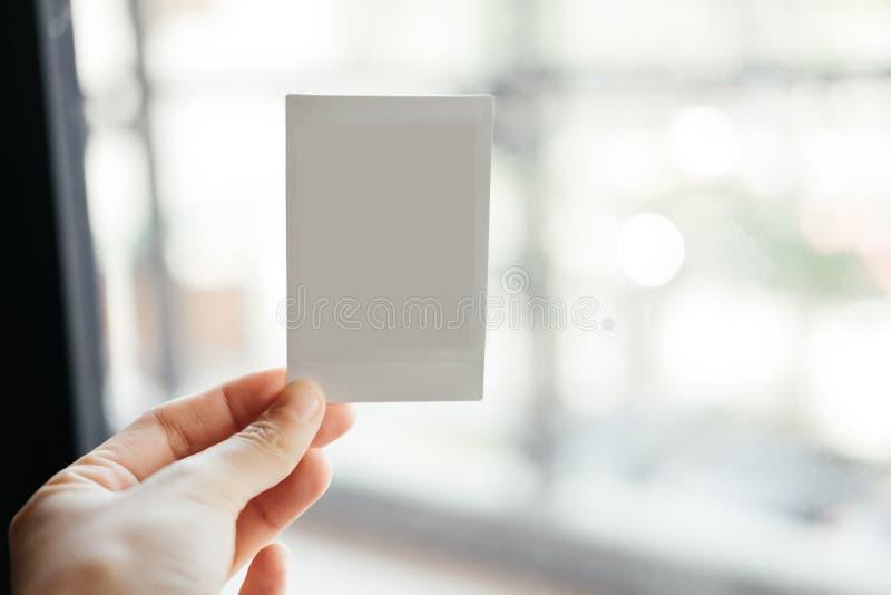 Bekläda beskådar hand av för innehavmellanrum för ung kvinna den polaroid- filmen HAV arkivbild