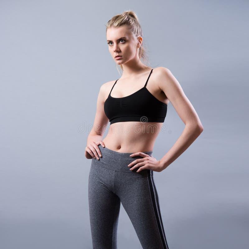 Beklär den bärande sporten för den härliga unga konditionkvinnan att posera arkivfoto