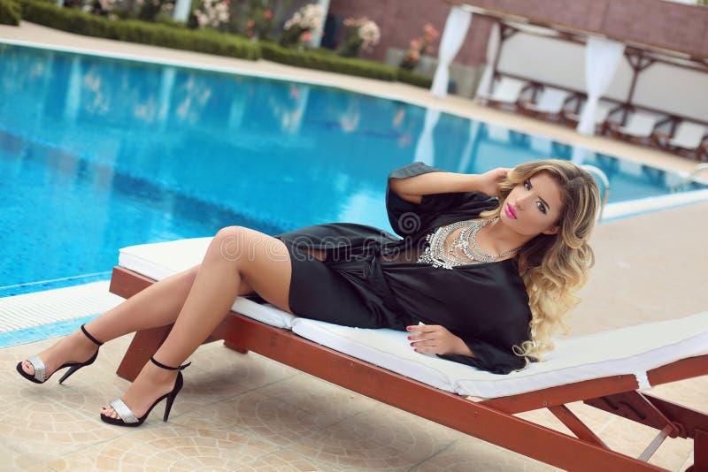 Beklär den sexiga flickamodellen för den lyxiga semesterorten i mode att koppla av på bea arkivbild