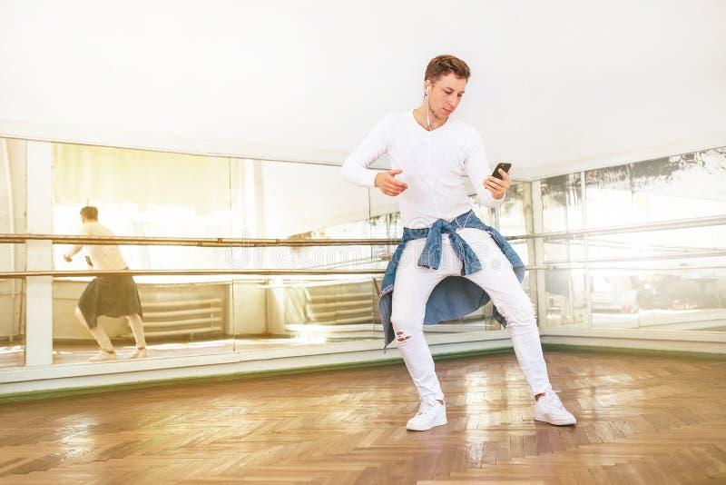 Beklär iklädd vit för modern konstdansaretonåringen att lyssna en musik med att använda för smartphone hörlurar och att dansa i d royaltyfria foton