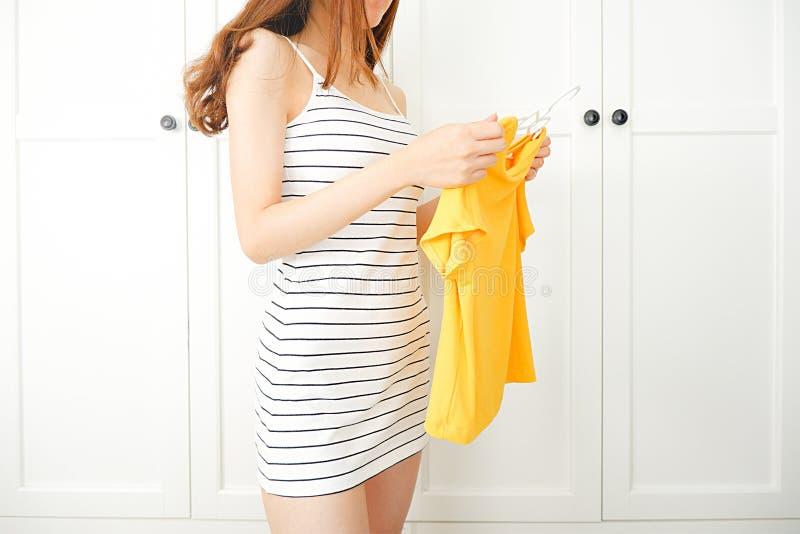 bekl?da, mode, stil och folkbegrepp Härlig sexig klänning för kvinnakläder som står i hemmastadd garderob för kläder kvinnligt v? royaltyfri bild