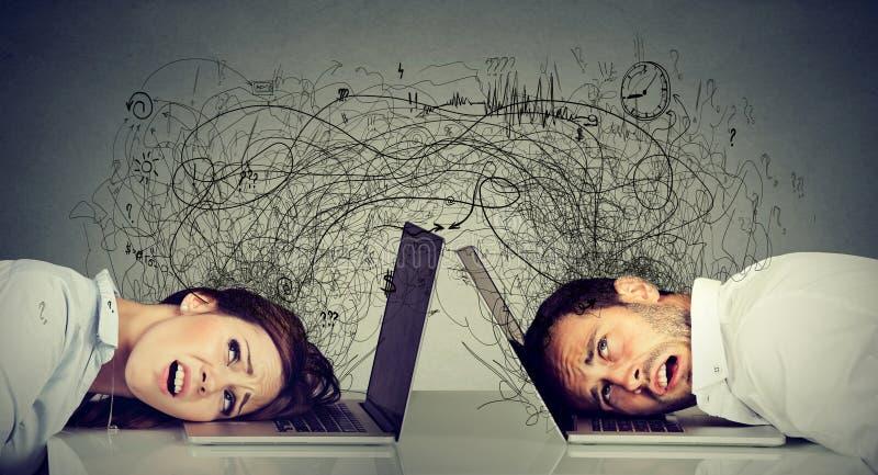 Beklemtoond bedrijfsvrouw en man rustend die hoofd op laptop zitting bij lijst met elkaar wordt gefrustreerd die met rommel van n stock foto's
