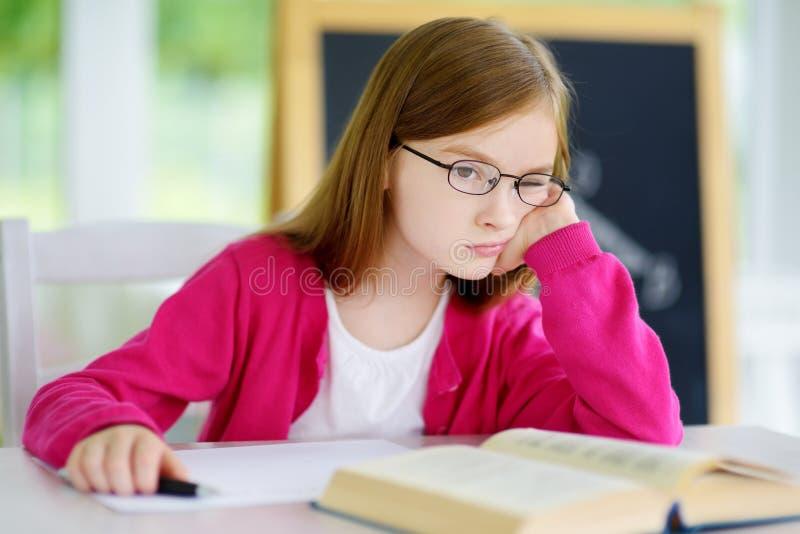 Beklemtoond en vermoeid schoolmeisje die met een stapel van boeken op haar bureau bestuderen royalty-vrije stock afbeeldingen