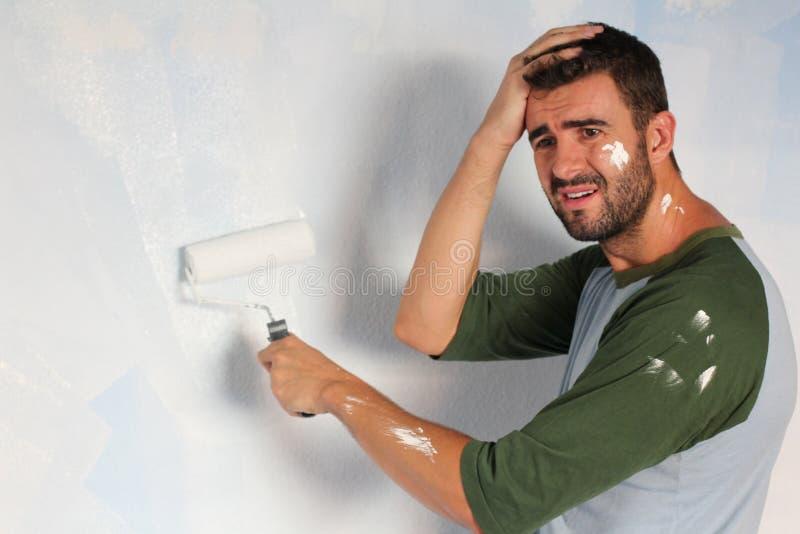 Beklemtoond uit mannetje die zijn huis met ruimte voor exemplaar schilderen royalty-vrije stock foto