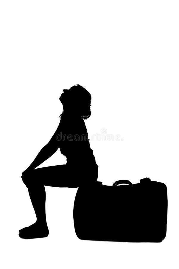 Beklemtoond vrouwensilhouet - zitting op bagage royalty-vrije stock foto