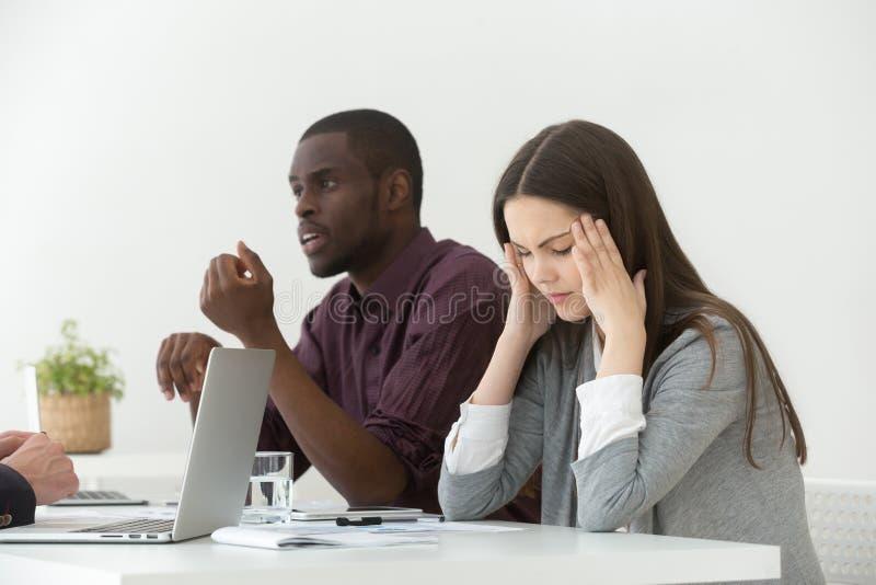 Beklemtoond wijfje die aan hoofdpijn tijdens commerciële vergadering lijden stock foto's