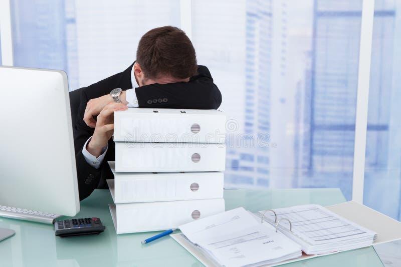 Beklemtoond zakenman rustend hoofd op bindmiddelen bij bureau stock afbeeldingen