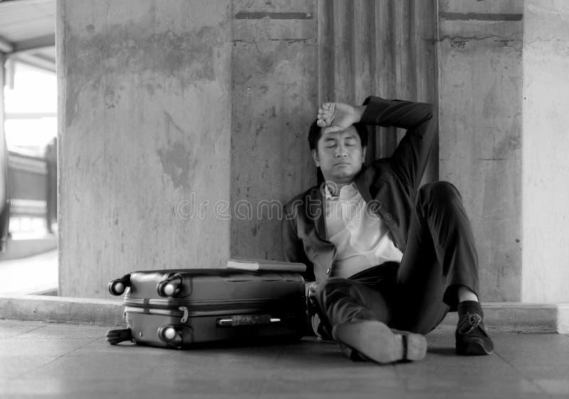 Beklemtoonde Aziatische zakenman failliet met het zitten bij openlucht stock fotografie