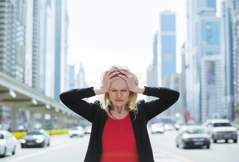 Beklemtoonde bedrijfsvrouw in de bezige stad royalty-vrije stock fotografie