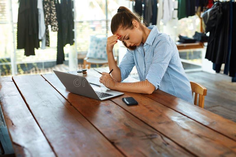 Beklemtoonde Bedrijfsvrouw die aan Laptop Computer werken Hoofdpijnpijn stock fotografie