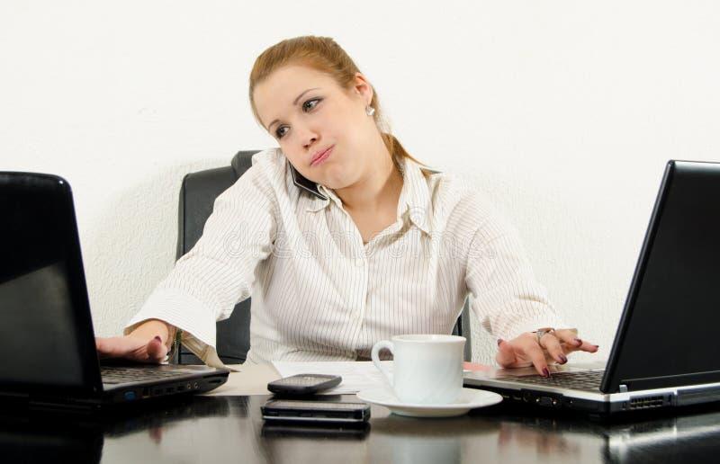 Beklemtoonde bedrijfsvrouwenmultitasking in haar bureau royalty-vrije stock fotografie