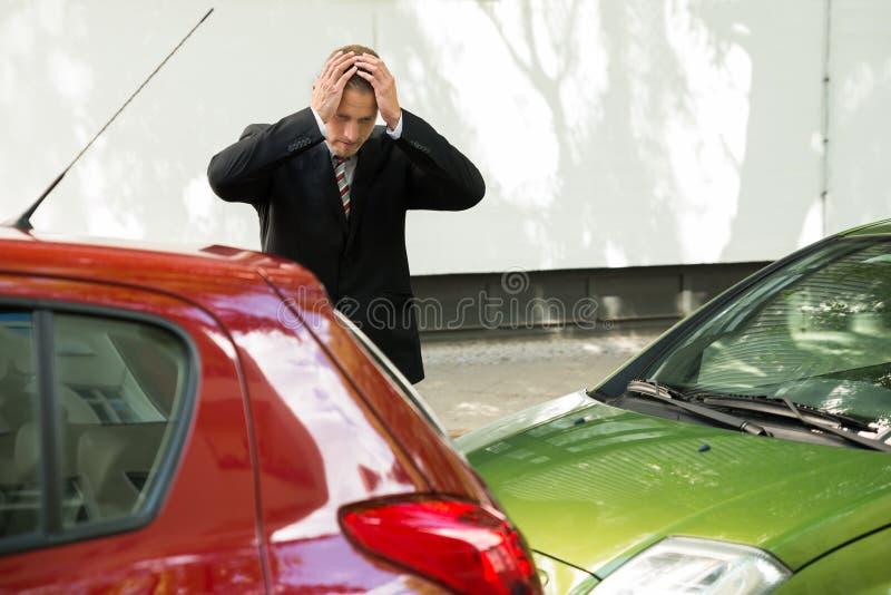 Beklemtoonde bestuurder die auto na verkeersbotsing bekijken royalty-vrije stock afbeelding