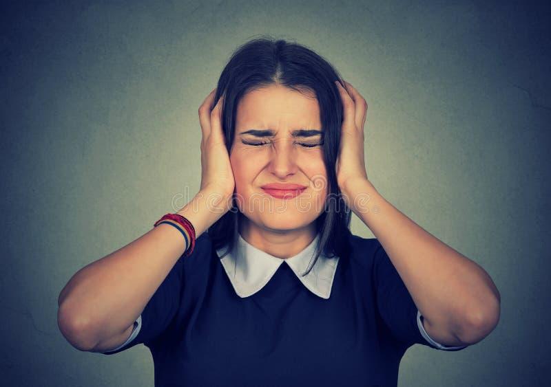 Beklemtoonde gefrustreerde vrouw die haar oren behandelen met handen stock foto's