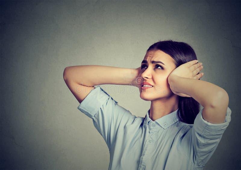 Beklemtoonde gefrustreerde vrouw die haar oren behandelen met handen stock afbeeldingen