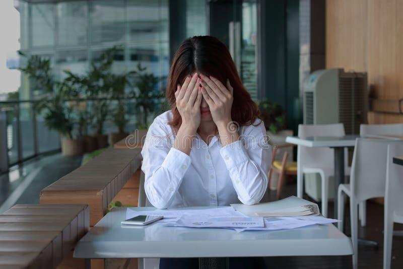 Beklemtoonde jonge Aziatische bedrijfsvrouw die gezicht behandelen met handen op het bureau in bureau stock afbeelding