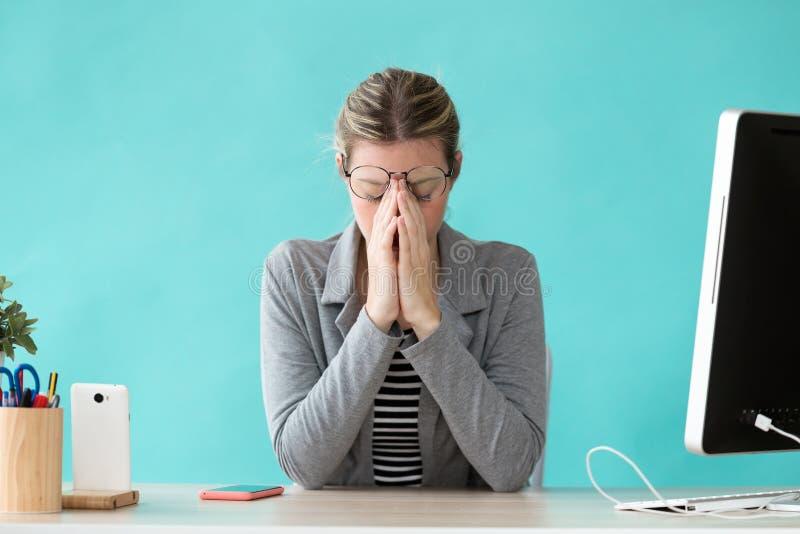Beklemtoonde jonge bedrijfsvrouw die aan bezorgdheid lijden terwijl het werken in het bureau stock foto's