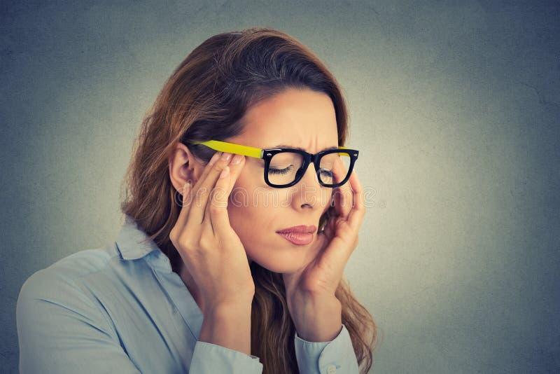Beklemtoonde jonge bedrijfsvrouw die hoofdpijn hebben stock afbeelding