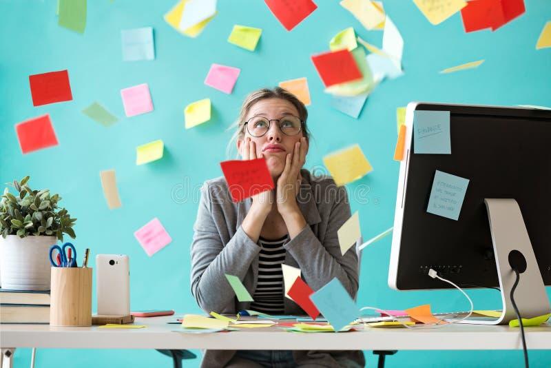 Beklemtoonde jonge bedrijfsvrouw die omhoog kijken die door post-its in het bureau wordt omringd stock foto