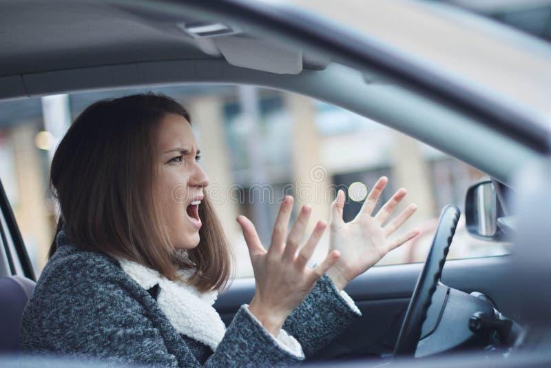 Beklemtoonde jonge onderneemster die haar auto drijven stock afbeelding