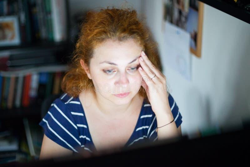 Beklemtoonde jonge vrouw die laat aan een computer werken stock afbeelding