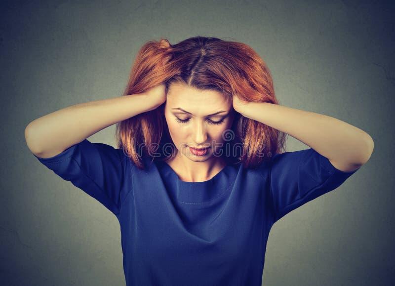Beklemtoonde jonge vrouw die met hoofdpijn neer kijken royalty-vrije stock fotografie