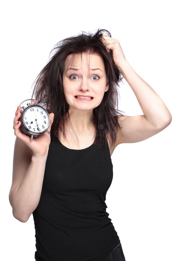 Beklemtoonde jonge vrouw met klok op wit stock afbeelding