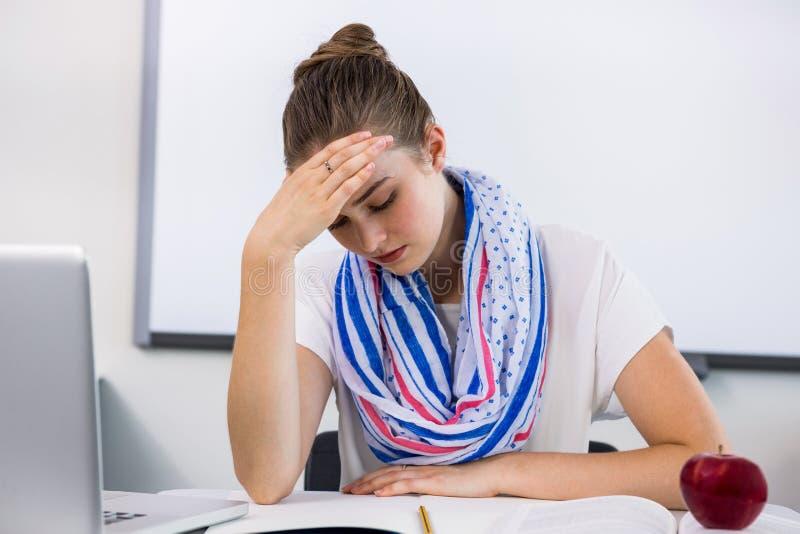 Beklemtoonde leraar die aan hoofdpijn in klaslokaal lijden stock fotografie