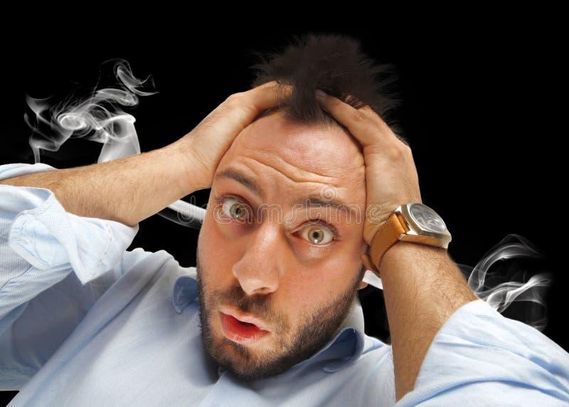 Beklemtoonde mens met rook die uit zijn oren komen stock foto