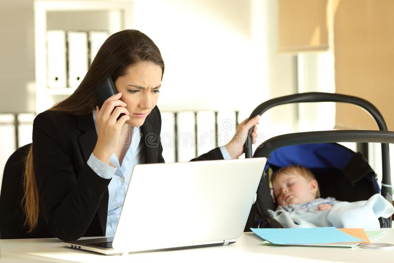 Beklemtoonde moeder die behandelend haar baby op kantoor werken stock foto