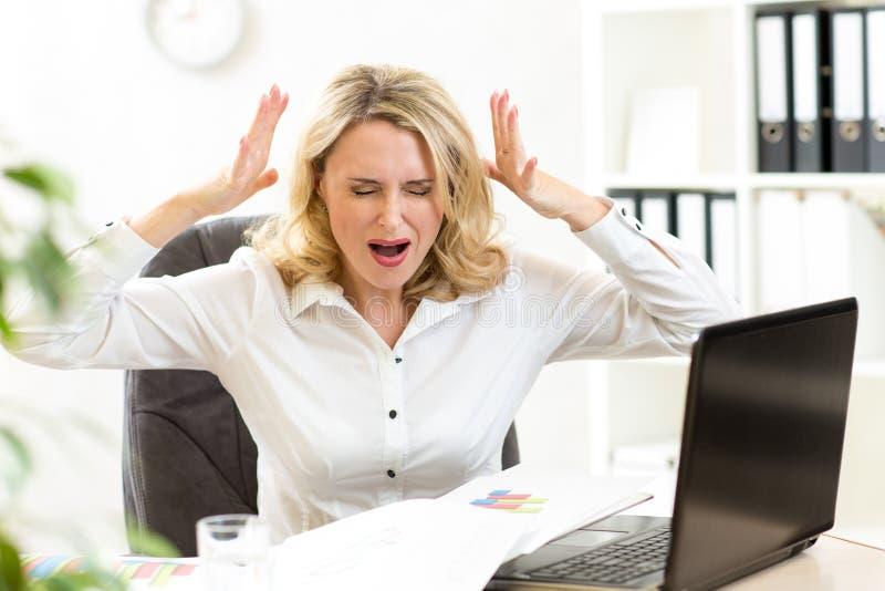 Beklemtoonde onderneemster die luid bij laptop gillen stock foto's