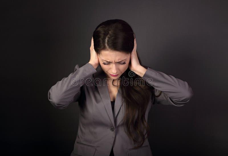 Beklemtoonde ongelukkige bedrijfsvrouw in grijze kostuum gesloten oren han stock afbeelding