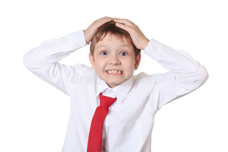 Beklemtoonde schooljongen die zijn hoofd, frustratie of vrees houden, isolat royalty-vrije stock afbeelding