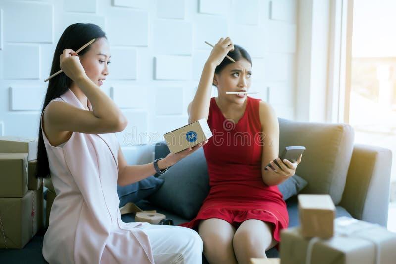 Beklemtoonde twee vrouweneigenaar die thuis bureau, de Aziatische vrouwelijke online, Kleine zaken hoofdpijn van het startonderne stock foto's