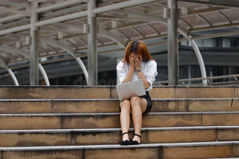 Beklemtoonde uitgeputte jonge Aziatische bedrijfsdievrouw met handen bij gezicht het voelen met baan wordt teleurgesteld of wordt stock afbeelding