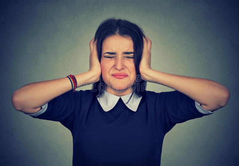 Beklemtoonde verstoorde vrouw gefrustreerd behandelend haar oren met handen royalty-vrije stock afbeelding