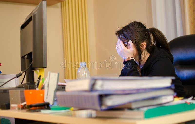Beklemtoonde vrouw aan het werk met computer voor haar stock afbeeldingen