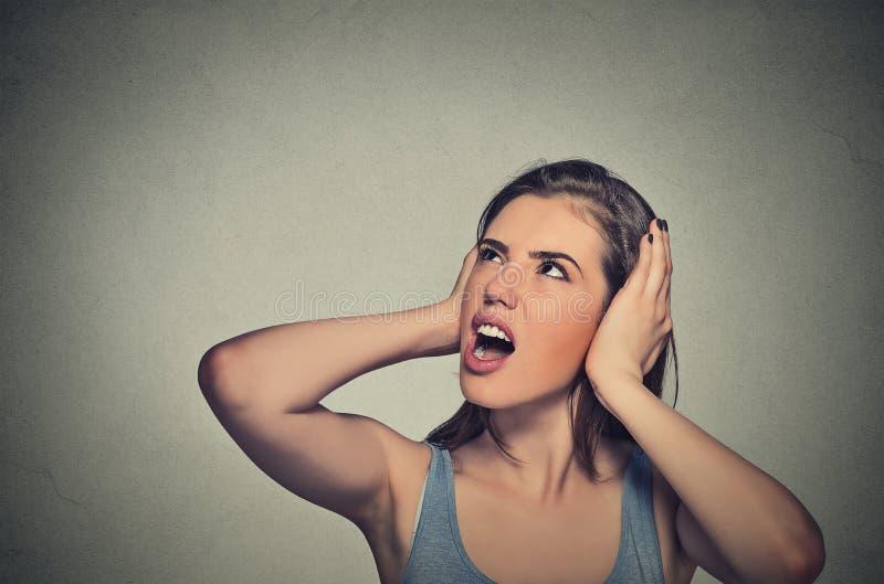 Beklemtoonde vrouw die haar oren behandelen die omhoog eruit zien stock afbeeldingen