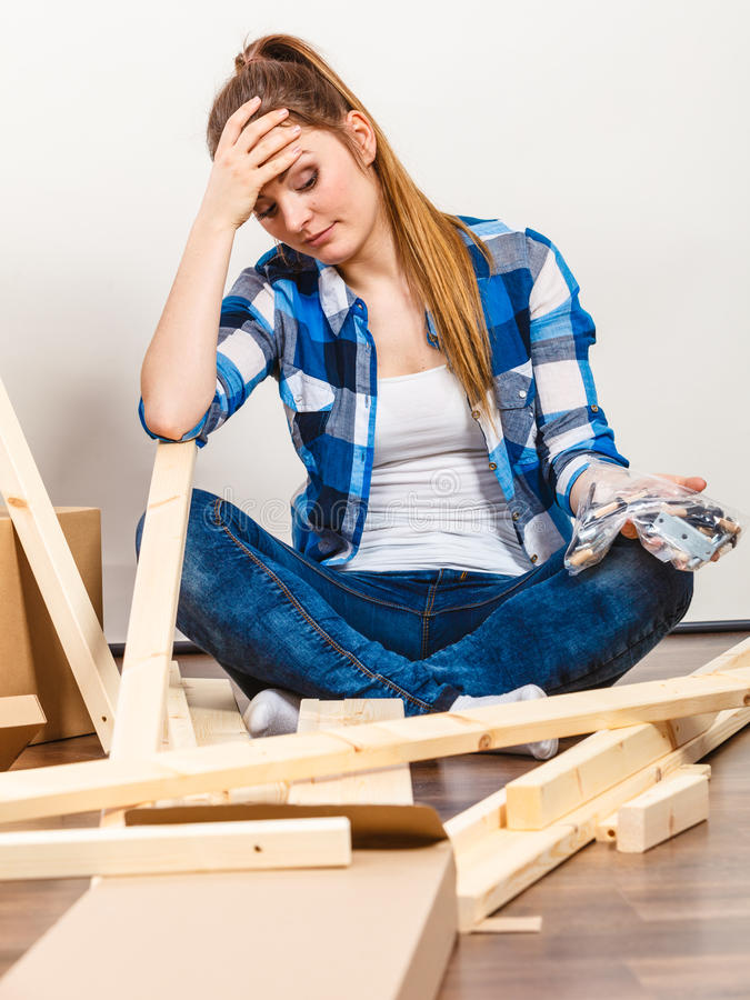 Beklemtoonde vrouw die houten meubilair assembleren DIY stock afbeeldingen