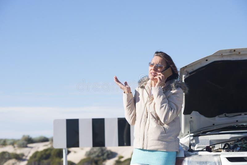 Beklemtoonde vrouw die hulp na autoanalyse telefoneren royalty-vrije stock foto's